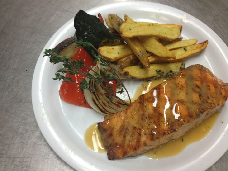 Grilled salmon with roasted potato and grilled vegetables and buerre blanc sauce.